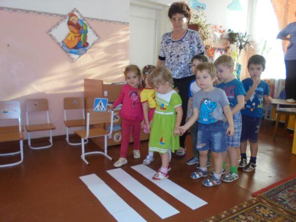 Дети и педагог стоят перед импровизированным пешеходным переходом в помещении группы