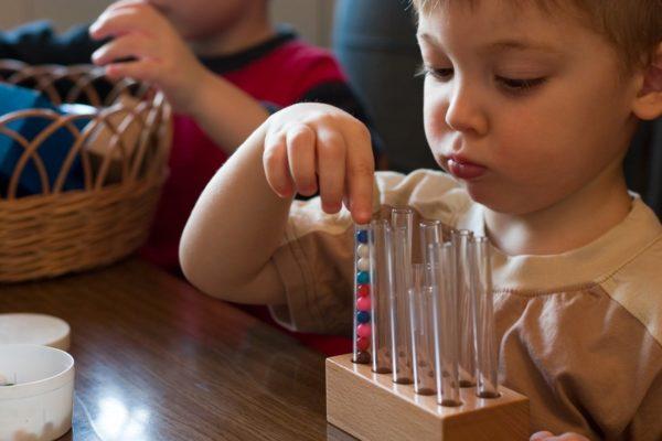Ребёнок проводит эксперимент с маленькими шариками и стеклянными пробирками
