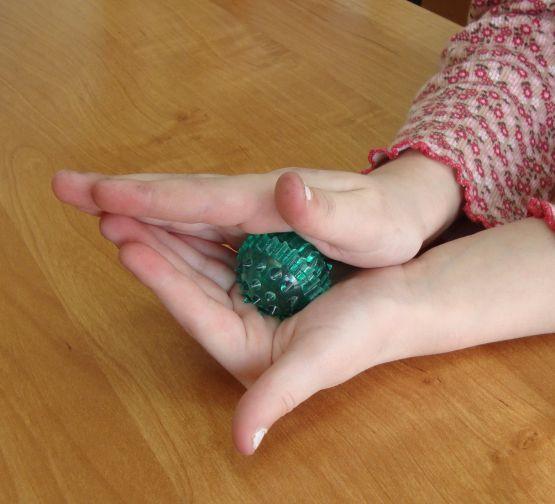 Ребёнок делает самомассаж ладошек с помощью мячика