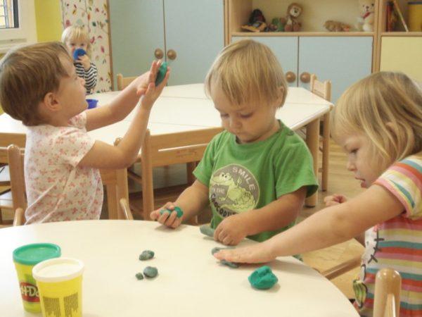Трое детей лепят из пластилина