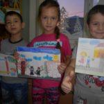 Трое детей с рисунками в руках