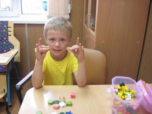 Мальчик делает упражнение для пальчиков