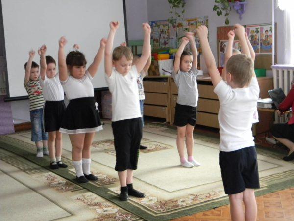 Дети стоят с поднятыми вверх руками, один мальчик показывает движения остальным
