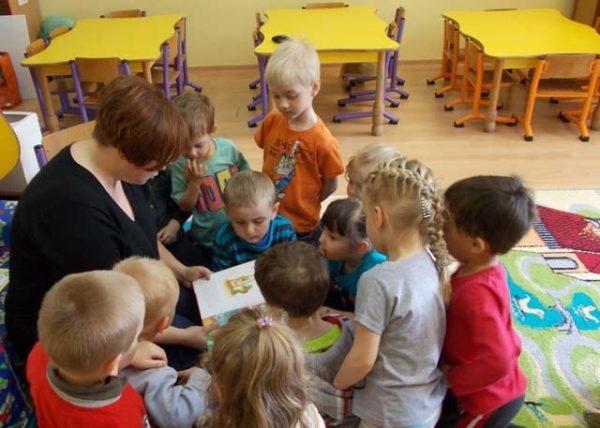 Воспитатель читает, дети стоят вокруг неё