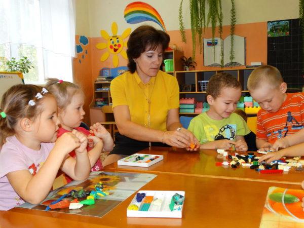 Воспитатель и дети лепят из пластилина