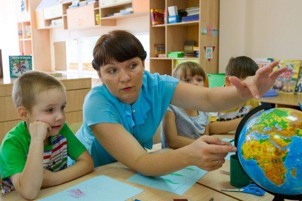 Воспитатель объясняет мальчику что-то на глобусе