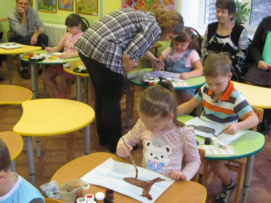 Воспитатель помогает детям рисовать
