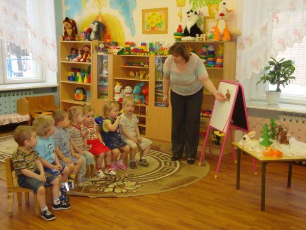 Воспитатель проводит беседу с детьми первой младшей группы