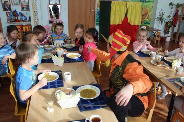 Воспитатель в костюме Буратино сидит за столом с детьми
