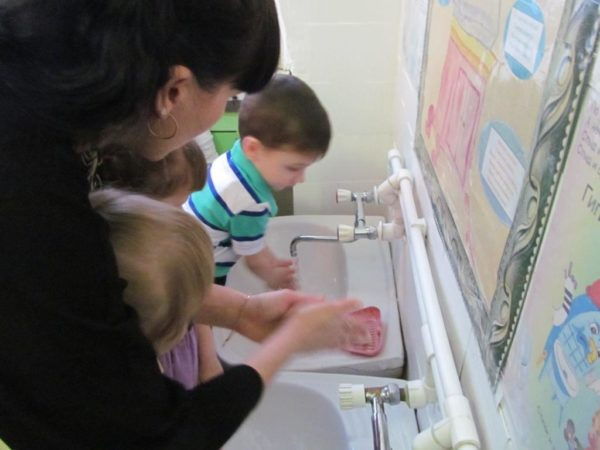 Воспитатель вместе с детьми моет руки
