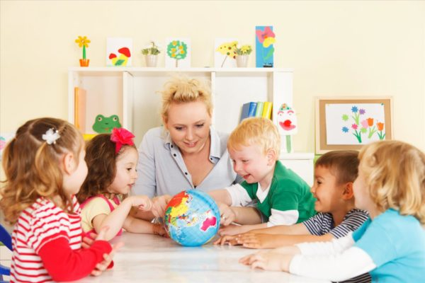 Воспитатель показывает улыбающимся детям глобус
