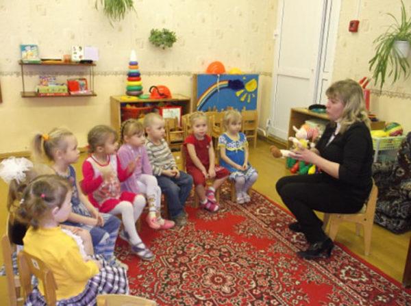 Воспитательница что-то рассказывает детям от лица игрушки