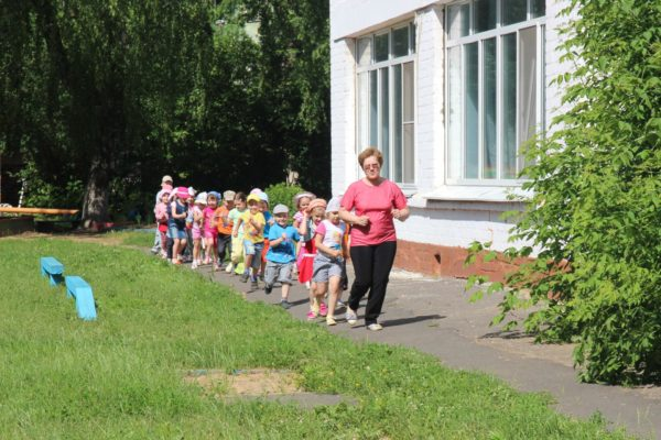 Дети идут спортивной ходьбой по территории детского сада