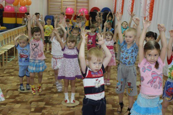 Дошкольники стоят с поднятыми вверх руками