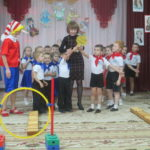 Команды детей с красными и синими галстуками и Буратино на физкультурном празднике