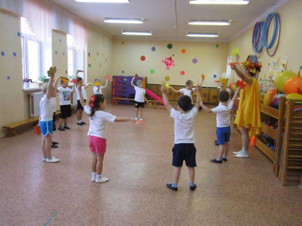 Дети и педагог в костюме Осени стоят в кругу и машут листочками