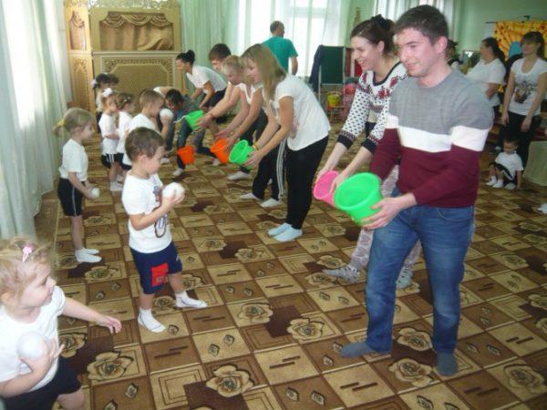 Дети бросают мячики в вёдра своим родителям