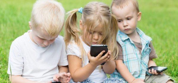 Дети дошкольного возраста сидят с мобильными телефонами и смотрят в экраны
