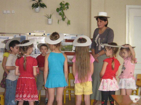 Дети и педагог в бумажных шляпах
