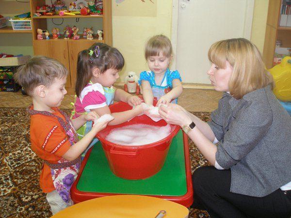 Дети и воспитатель делают опыт в тазике с пеной