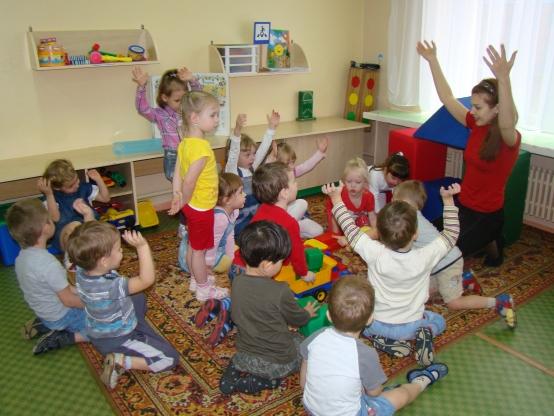 Дети и воспитательница подняли руки вверх
