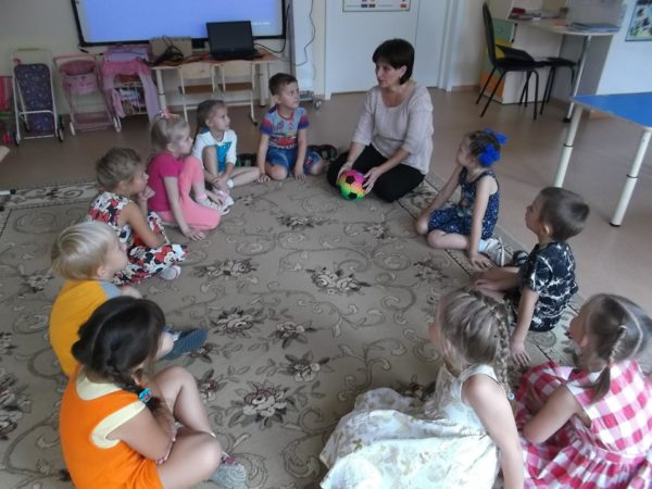 Дети и воспитательница с мячом в руках сидят в кругу на ковре