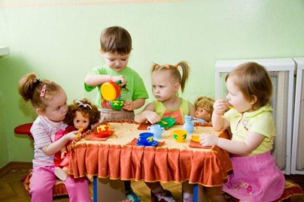 Дети играют вместе с куклами в чаепитие