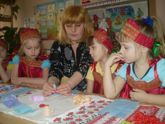 Девочки в национальных костюмах наблюдают за созданием народной куклы