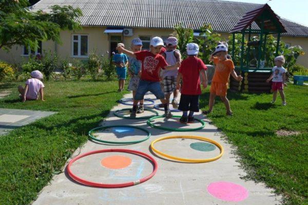 Дети прыгают из обруча в обруч на участке детского сада