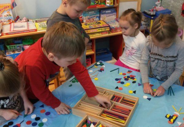 Дети раскладывают счётные палочки и плоские геометрические фигуры