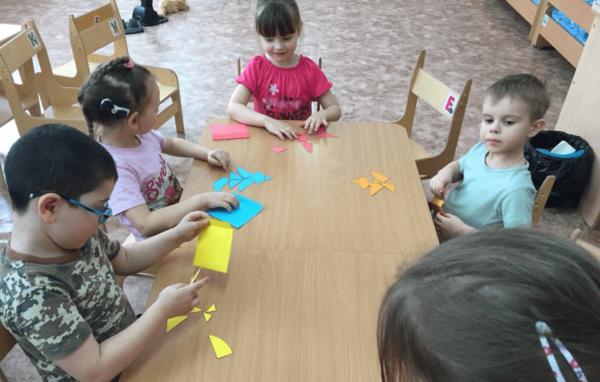 Дети, сидя за столом, собирают изображения из цветных бумажных фигур