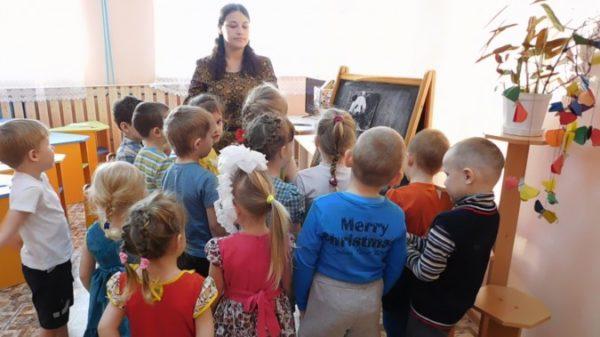 Дети стоят вокруг воспитательницы