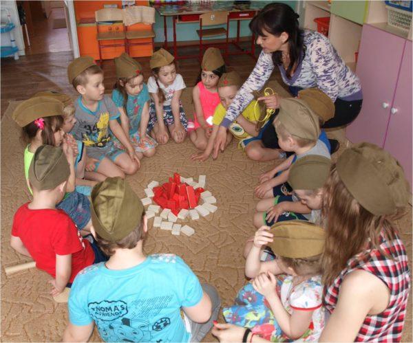 Дети в пилотках и педагог сидят на полу вокруг импровизированного костра