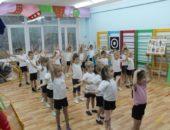 Дети в спортивной форме выполняют упражнение с поднятыми вверх руками