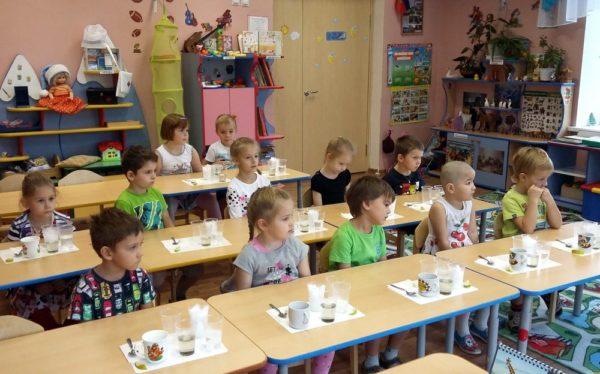 Дети сидят за столиками с материалами для опытов с водой