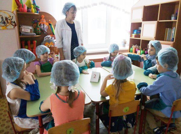 Дети за столом и педагог в шапочках