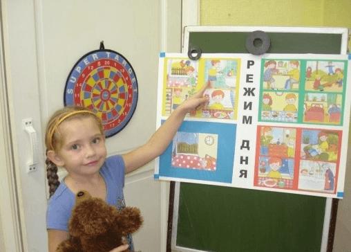 Девочка показывает на картинки, посвящённые соблюдению режима дня