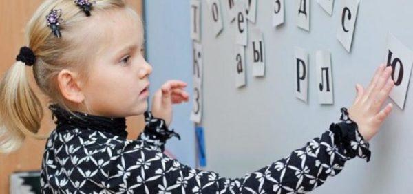 Девочка располагает на доске буквы на карточках