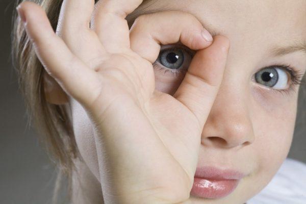 Девочка сделала пальцы кружком и смотрит через них