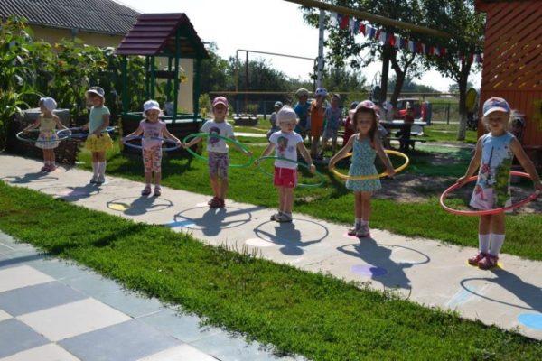 Девочки крутят обручи на участке детского сада