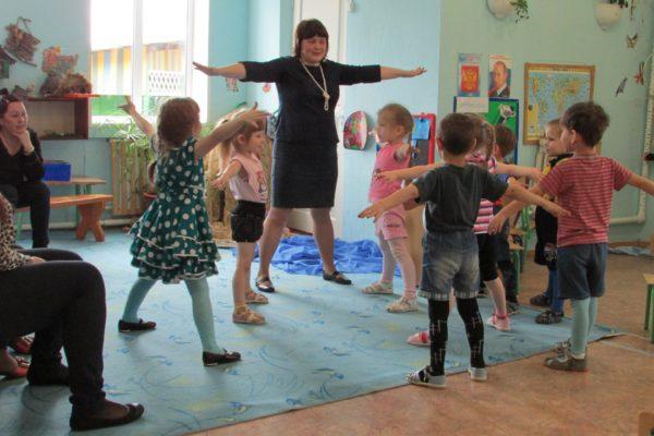 Дети и педагог стоят на ковре, вытянув руки в стороны