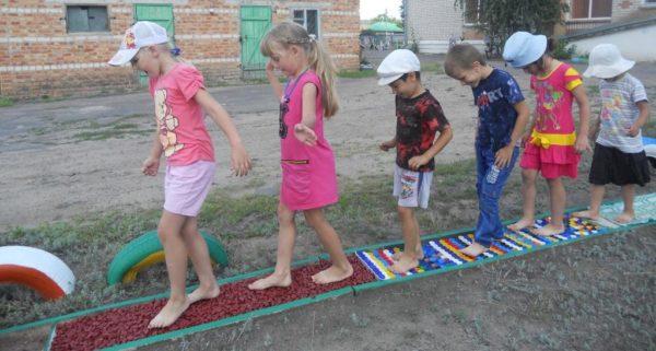 Дети босиком идут по гимнастической дорожке на территории ДОУ
