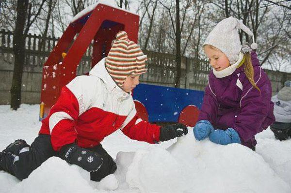Двое детей играют в снегу