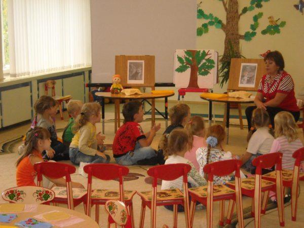 Дети, сидя на ковре, слушают педагога