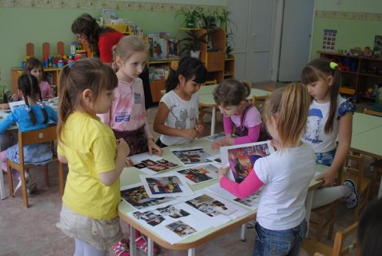 Девочки рассматривают фотографии с людьми разных национальностей