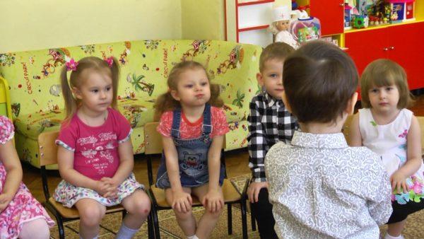 Мальчик перед детьми, сидящими на стульях