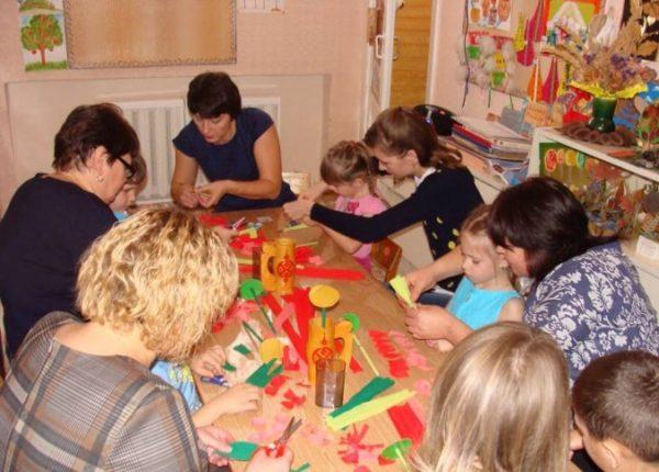 Дети и родители делают поделки из цветной бумаги