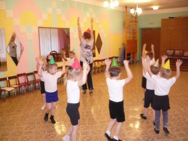Дети и педагог ходят по кругу с поднятыми вверх руками
