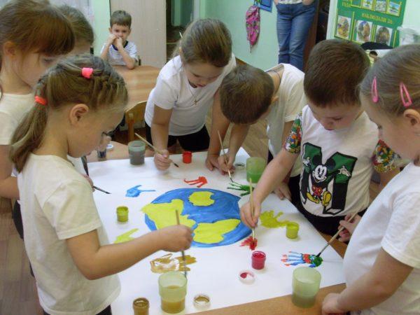 Дети рисуют красками коллективный плакат с изображением земного шара и цветными ладошками