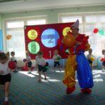 Дети с мячиками в руках и педагог в костюме Петрушки
